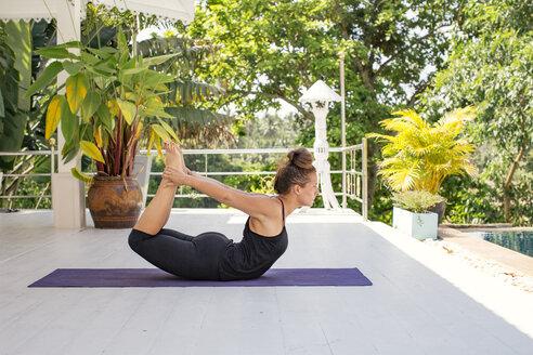 Woman practicing yoga on terrace - MOMF00439