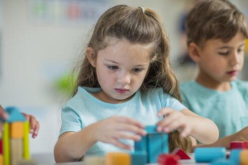 Focused girl playing with building blocks in kindergarten - ZEF15431
