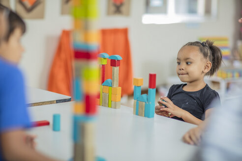 Girl looking at tower of building blocks in kindergarten - ZEF15437