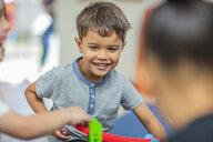 Happy boy playing with other children in kindergarten - ZEF15440