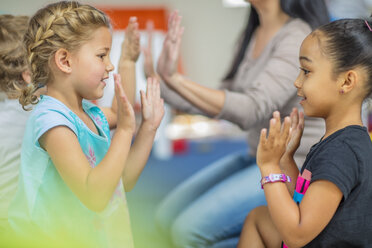 Happy children and pre-school teacher clapping hands in kindergarten - ZEF15443
