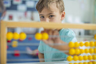 Boy in kindergarten using abacus - ZEF15446