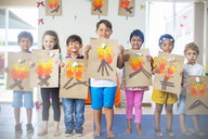 Portrait of smiling children presenting images of fire in kindergarten - ZEF15452