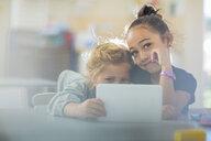 Portrait of two smiling girls sharing mini tablet in kindergarten - ZEF15461