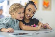 Two girls sharing headphones in kindergarten - ZEF15464