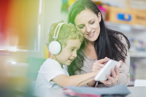 Pre-school teacher showing mini tablet to boy with headphones in kindergarten - ZEF15467