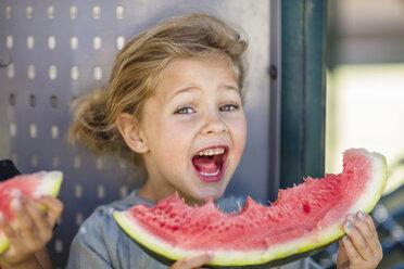 Portrait of happy girl eating a watermelon in kindergarten - ZEF15476