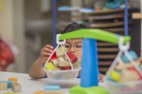 Boy playing with toy scales in kindergarten - ZEF15482