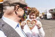 Portrait of hasmiling senior woman presenting gingerbread heart on fair - UUF13738