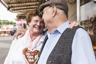 Happy senior couple with gingerbread heart on fair - UUF13741