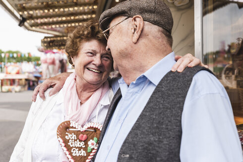 Happy senior couple with gingerbread heart on fair - UUF13741