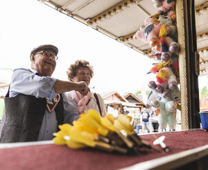 Senior couple having fun on fair - UUF13750