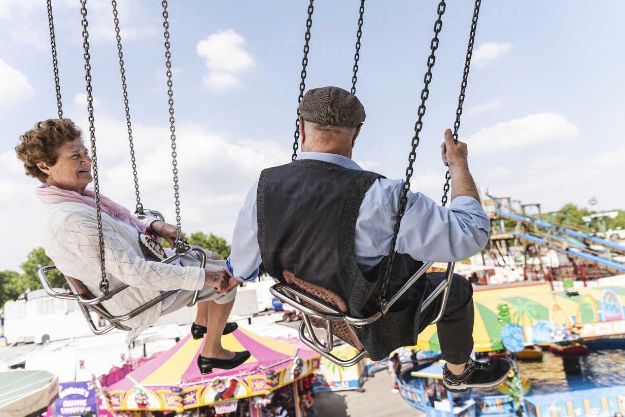 Senior couple hand in hand on chairoplane at funfair - UUF13756 - Uwe Umstätter/Westend61