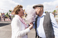 Senior couple on fair eating together  cotton candy - UUF13759