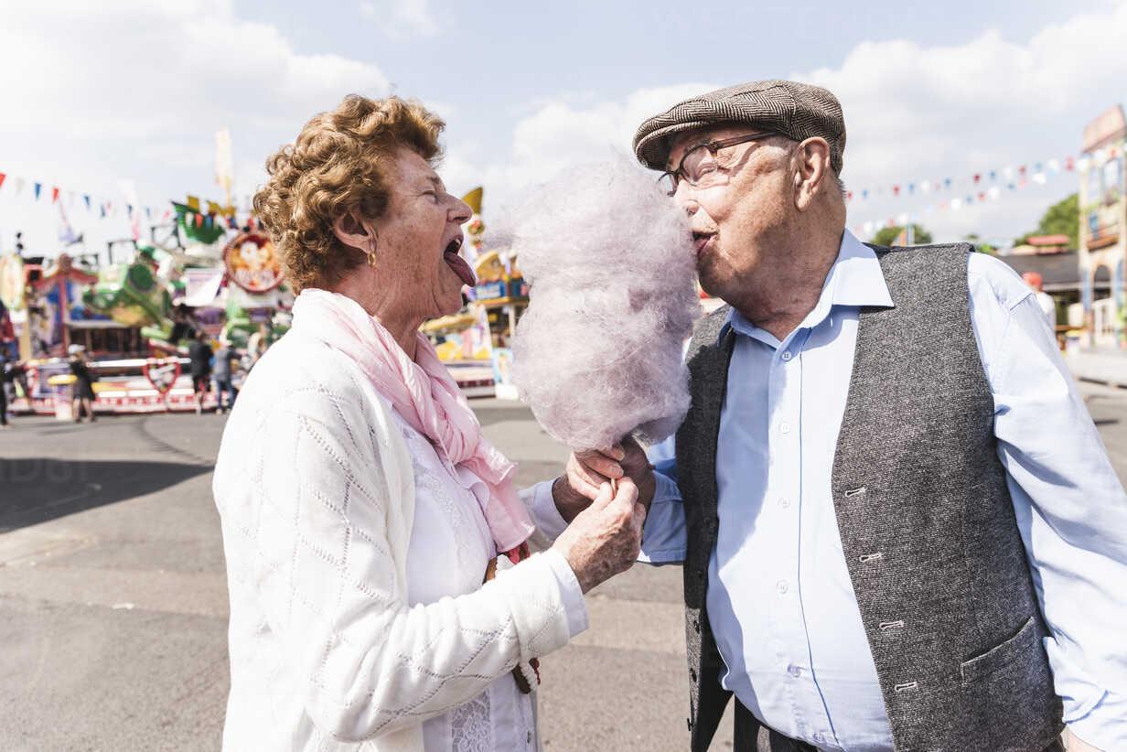 Senior couple on fair eating together  cotton candy - UUF13759 - Uwe Umstätter/Westend61