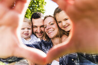 Portrait of happy family looking through finger frame - UUF13762