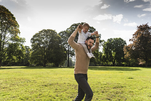 Happy father carrying son on shoulders in a park - UUF13780