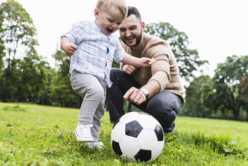 Happy father playing football with son in a park - UUF13783
