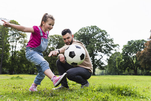 Father playing football with daughter in a park - UUF13786