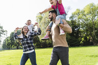 Happy parents carrying children on shoulders in a park - UUF13789
