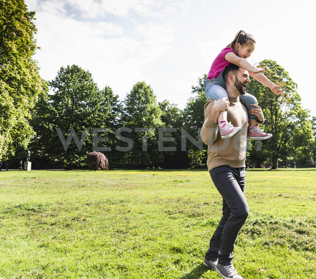 Happy father carrying daughter on shoulders in a park - UUF13792