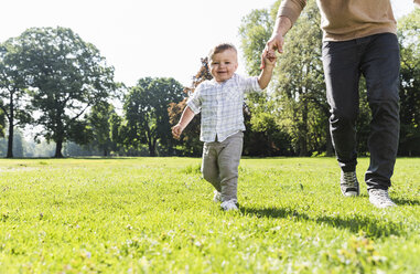 Father walking hand in hand with son in a park - UUF13795