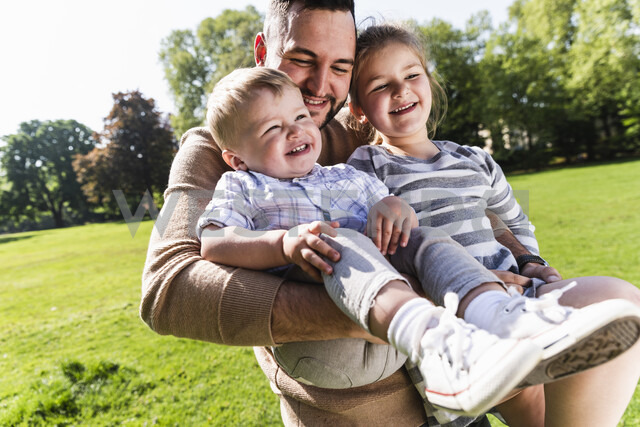 Happy father carrying children in a park - UUF13798