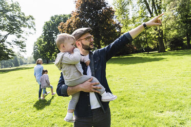 Father carrying and talking to son in a park - UUF13813