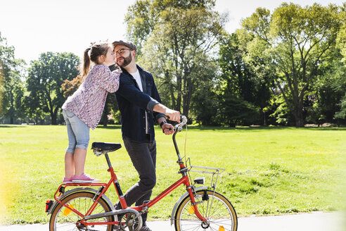 Daughter kissing father with bicycle in a park - UUF13816