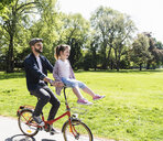 Happy father riding bicycle with daughter sitting on handlebar in a park - UUF13819