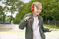 Boy with headphone dancing while listing to music on smartphone - PDF01636