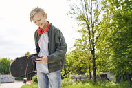 Boy with headphones and skateboard using smartphone - PDF01642