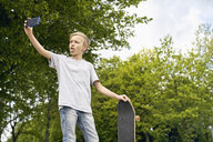 Boy with skateboard taking selfies with smartphone - PDF01645