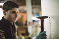 Man hammering a dowel in a wall - RAEF02040