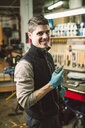 Portrait of a smiling mechanic in his workshop - RAEF02043