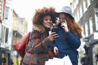 Two young women in street, looking at smartphone, laughing - CUF09282