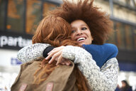 Two young women hugging at train station - CUF09288