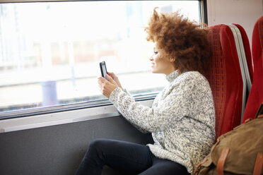 Woman taking photo with mobile phone from train, London - CUF09294
