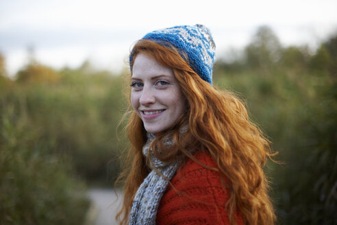Portrait of red haired woman looking over shoulder at camera smiling - CUF09297
