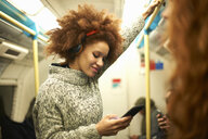 Young woman on subway train, looking at smartphone - CUF09306
