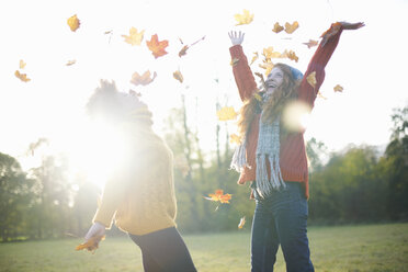 Friends throwing autumn leaves in air - CUF09312