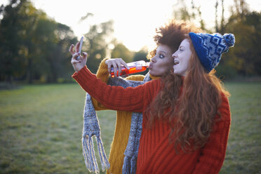Two young women, in rural setting, taking selfie, using smartphone - CUF09339