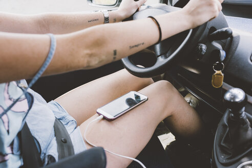 Mid section of young woman driving vehicle with smartphone on her lap - CUF09342