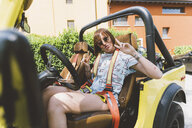 Portrait of young woman on road trip in off road vehicle giving peace sign, Como, Lombardy, Italy - CUF09345