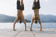 Two young men doing handstands on waterfront, Lake Como, Lombardy, Italy - CUF09348