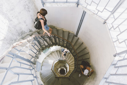 High angle view of three young adults moving down spiral staircase, Como, Lombardy, Italy - CUF09357