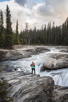 Woman standing at edge of waterfall, looking at view, Natural Bridge Falls, Kicking Horse River, Yoho National Park, Field, British Columbia, Canada - CUF09615