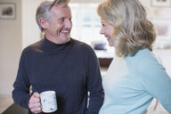 Smiling mature couple talking and drinking coffee - HOXF03521