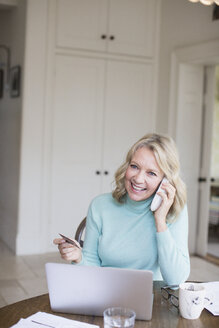 Smiling mature woman with credit card talking on telephone at laptop - HOXF03542