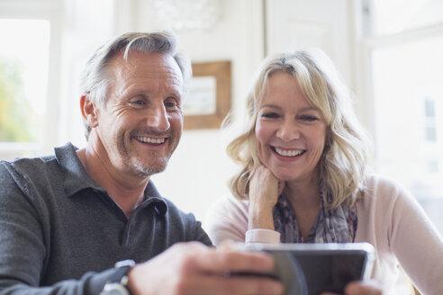 Smiling mature couple using smart phone - HOXF03545